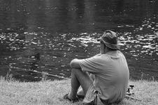 Free Man Sitting Facing Body Of Water Stock Photo - 113907820