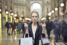 Free Woman Wearing Black Coat Holding Assorted-color Shopping Bags On Building Stock Images - 113907844