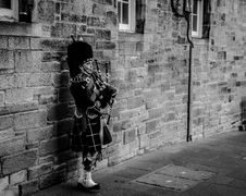Free Person Using Bagpipes Near Wall In Grayscale Photography Royalty Free Stock Images - 113947479