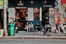 Free Three People Sitting On Chairs Outside Coffee & Tea House Near Motorcycles Royalty Free Stock Images - 113947599