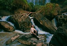 Free Photo Of Man Sitting On Gray Rock Surrounded By Water Falls Stock Photo - 113947680