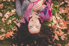 Free Woman Lying Down On Green Grass Field Holding Brown Leaf Stock Images - 113947714