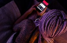 Free Woman With Purple Braided Hair Holding An Android Smartphone Stock Image - 114021411