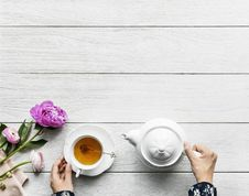 Free Person Holding White Ceramic Teapot On White Wooden Surface Stock Photo - 114021480