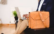 Free Person Wearing Blue Suit Beside Crossbody Bag And Using Macbook Royalty Free Stock Photo - 114021495