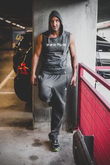 Free Man Wearing Black Hooded Top And Black Adidas Pants Leaning On Gray Wall Stock Image - 114264561