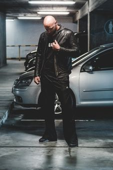 Free Man In Black Leather Jacket Standing In Front Of Gray Car Stock Photography - 114264572