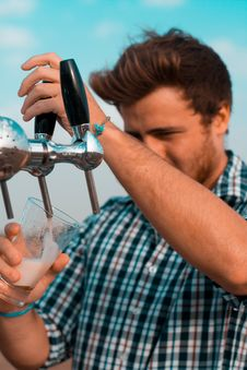 Free Man Holding Black Beer Tap Handle Pouring Beer On Clear Glass Stock Photo - 114321180