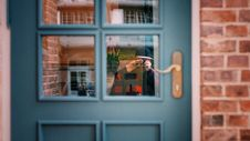 Free Man In Black Sweater Taking Photo Of Blue Door Stock Image - 114321201