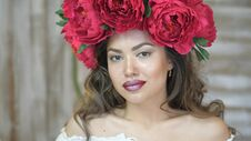 Free Girl Posing In Front Of Camera. Young Woman In A Wreath Of Scarlet Peonies On Her Head, Dark Long Curly Hair Descends On Stock Images - 114373644