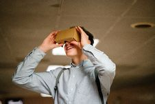Free Man In Grey Dress Shirt Using Brown Cardboard Vr Glasses Stock Photography - 114378592
