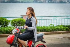 Free Woman Riding Red Motor Scooter Stock Photography - 114378722