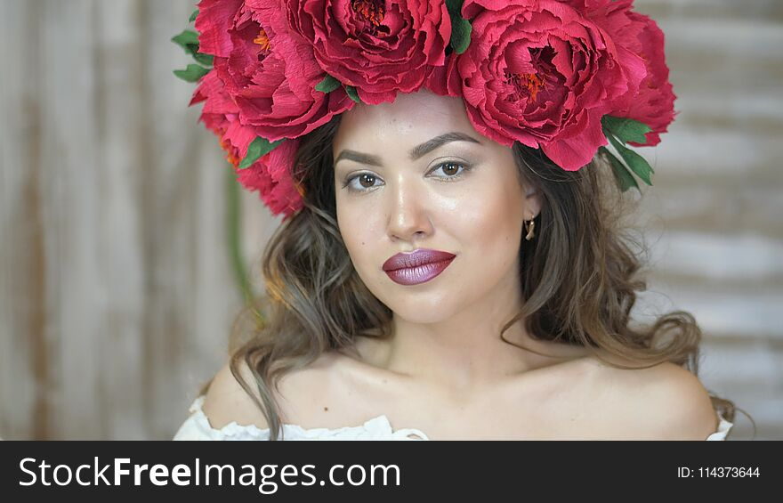 Girl posing in front of camera. young woman in a wreath of scarlet peonies on her head, dark long curly hair descends on