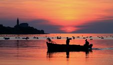 Free Silhouette Of Two Men On Boat Under Orange Sky Royalty Free Stock Image - 114443136