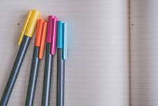 Free Yellow, Orange, Pink, And Blue Coloring Pens On White Notebook Stock Photo - 114443310