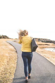 Free Woman Wears Yellow Bubble Jacket Walk Through Gray Asphalt Way Royalty Free Stock Photos - 114510568