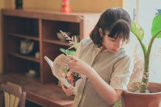 Free Woman In Grey Button-up Short-sleeved Top Holding Book Stock Image - 114510661