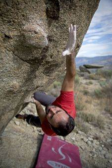 Free Man Climbing On Gray Concrete Peak At Daytime Stock Photo - 114510730
