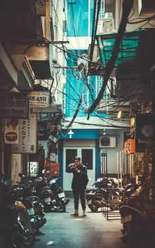 Free Man Standing On Concrete Road With Parked Motorcycles While Holding Dslr Camera Stock Images - 114510744