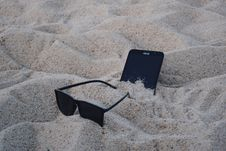Free Black Wayfarer-style Sunglasses Beside Black Asus Android Smartphone On Brown Sand Stock Photos - 114603023