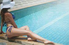 Free Woman Wearing Blue Bikini Set Sitting Beside Pool Royalty Free Stock Image - 114603206