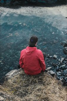 Free Man In Red Hoodie Sitting On Cliff Stock Photography - 114603252