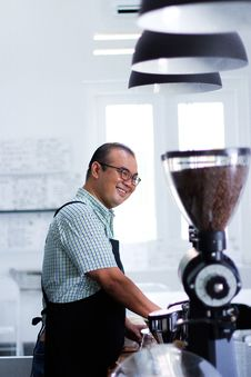 Free Man Wearing Plaid T-shirt And Black Apron In Front Of Coffeemaker Stock Images - 114677804