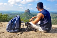 Free Man Sitting On Top Of Gray Cliff Mountain Beside Backpack, Water Bottle, And Camera Royalty Free Stock Photo - 114677855