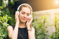 Free Woman Wearing Black Sleeveless Dress Holding White Headphone At Daytime Stock Photos - 114750793