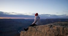 Free Person Wearing Gray Hooded Jacket And Black Pants Sitting On Mountain Cliff During Sunset Stock Photo - 114750880