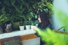 Free Woman Holding White Clay Pot With Green Plant Sitting Near White Painted Wall Stock Images - 114750904