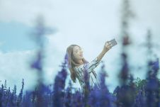 Free Woman In Black And White Dress Shirt Taking Photo On Lavender Flower Field At Daytime Stock Photo - 114750920