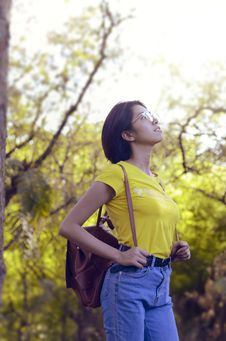 Free Woman Wearing Yellow Shirt And Looking Up Surrounded By Trees Stock Photo - 114751040