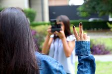 Free Woman Holding Camera While Taking Picture Of A Woman With A Peace Finger Sign Stock Photo - 114751210