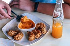 Free Person In Front Of Table With Fried Dumplings And Soda Bottle Royalty Free Stock Images - 114825529