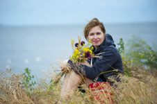 Free Woman Sitting On Grass Holding Flowers Wearing Black Hoodie Royalty Free Stock Photo - 114825625