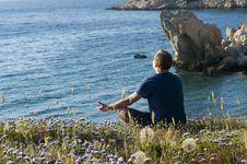 Free Man Sitting On Flower Fields Facing Ocean Stock Image - 114825631
