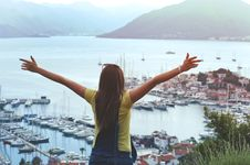 Free Woman Raising Her Hands Facing Cityscape Near Body Of Water Royalty Free Stock Images - 114825639