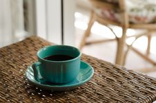 Free Blue Coffee Cup With Saucer Filled With Coffee On Top Of Wicker Table Royalty Free Stock Photos - 114825688