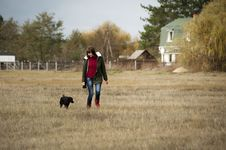 Free Woman Wearing Brown Zip-up Jacket And Blue Denim Jeans Walking Beside Short-coated Black Dog At Daytime Royalty Free Stock Images - 114825699