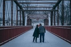 Free Couple Kissing On Bridge Covered With Snow Stock Photo - 114943970