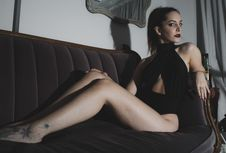 Free Photography Of A Woman Sitting On Couch Royalty Free Stock Images - 115013019