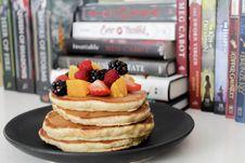 Free Pancake On Black Plate Near Books Stock Image - 115111021