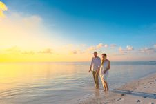 Free Couple Walking On Seashore Wearing White Tops During Sunset Stock Image - 115111061