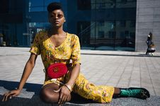 Free Woman In Yellow Floral Jumpsuit Sitting On Concrete Floor Royalty Free Stock Photography - 115111087