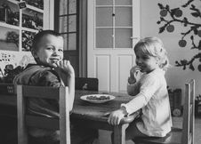 Free Grayscale Photo Of Two Kids Sitting On Dining Table Chairs Stock Image - 115203161