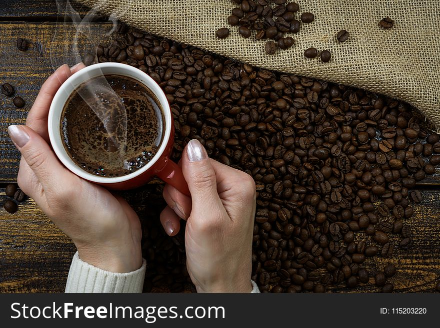 Person Holding Red Cup of Coffee Cup With Coffee Above Coffee Beans