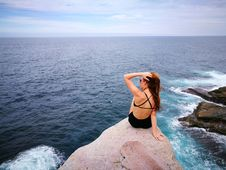 Free Woman In Black Swimwear Set Sitting On Top Of Gray Rocky Cliff Facing Body Of Water Royalty Free Stock Image - 115423766