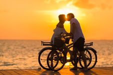 Free Photography Of Man Wearing White T-shirt Kissing A Woman While Holding Bicycle On River Dock During Sunset Royalty Free Stock Image - 115628136