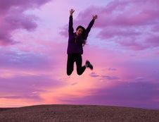 Free Smiling Woman Wearing Black Jacket And Pants Jumping In Brown Open Field Stock Photography - 115628352